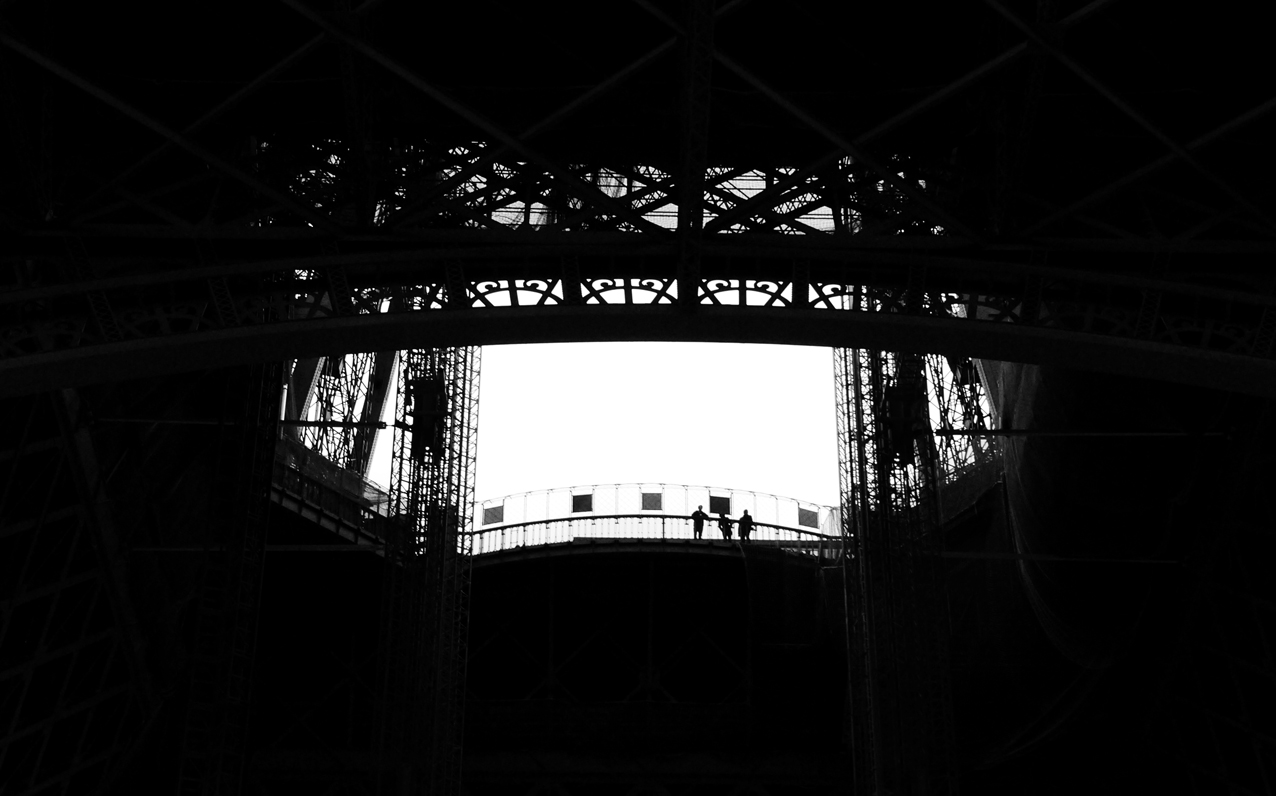 A view from underneath the Eiffel tower, looking up at some tourists enjoying the view over the city.