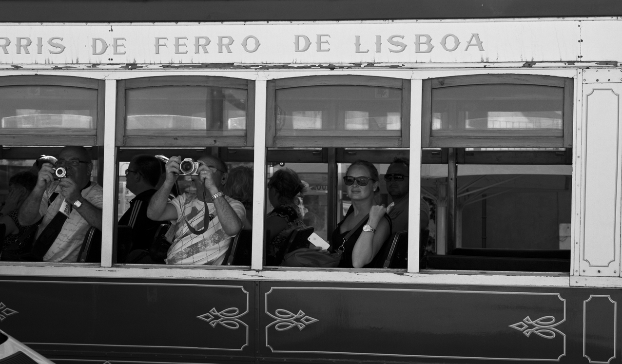 Tourists enjoying the view from the tram in Lisbon, Portugal. Street Photography in Lisbon.