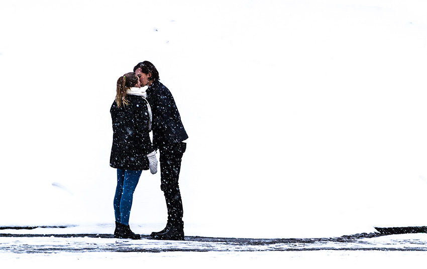 Winter Love - a young couple kissing in the snow, Street Photography